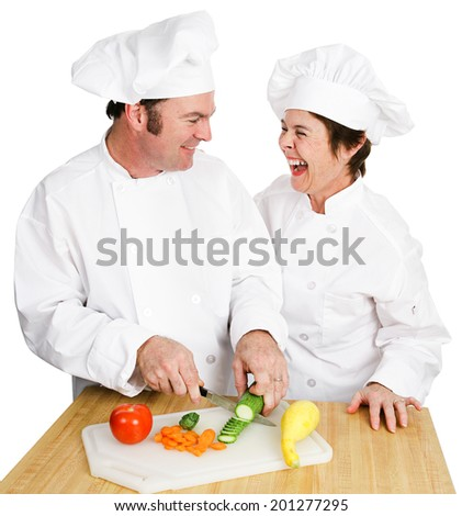Two chefs working together in the kitchen and laughing as they cut up vegetables. Isolated on white.   - stock photo