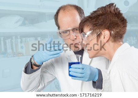 Two Chemists are smelling the blue Liquid. - stock photo
