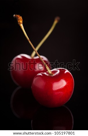two cherries on black background - stock photo
