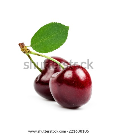 two cherries with a green leaf isolated closeup - stock photo