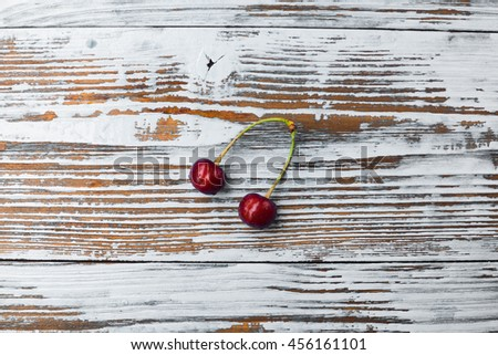 Two cherry on old wood. Healthy and tasty food on white background. - stock photo