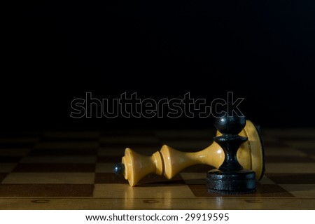 Two chessmen on a chessboard, black background