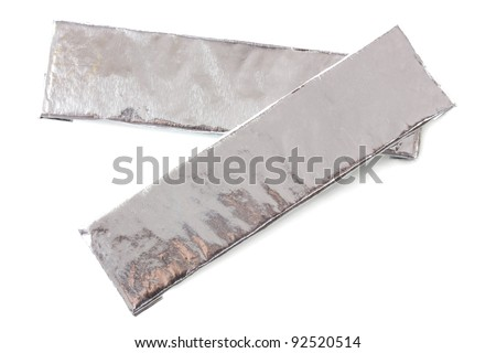 two chewing gums wrapped in standard silver foil, isolated on white