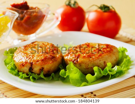 Two chicken cutlets on the green leaf lettuce. Decorated with fresh vegetables. - stock photo