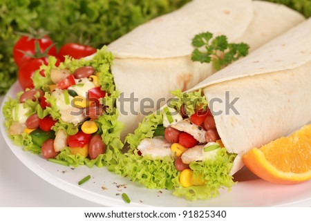 Two Chicken wrap sandwiches filled with beans, lettuce and corn