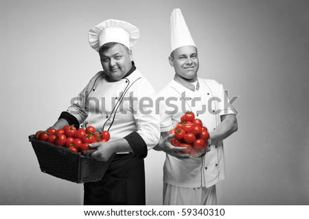 Two chief with tomato - stock photo