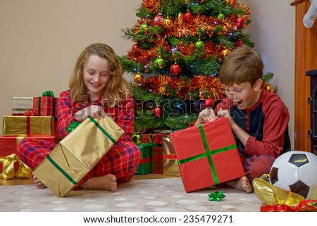 Two children, a boy and a girl, opening their presents on Christmas morning. - stock photo