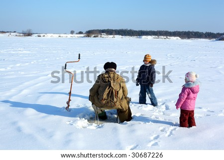 Two children and fisherman on frozen river - stock photo