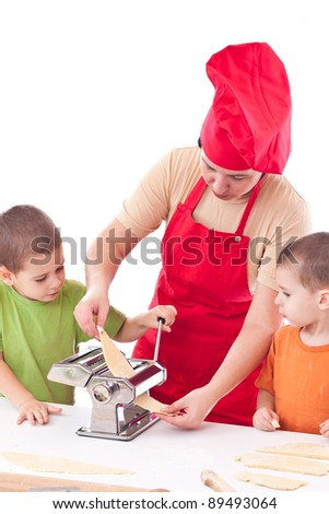Two children and their mother with a preparation pasta together in the kitchen - stock photo