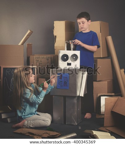 Two Children are building a metal robot from cardboard boxes with tools and books for an imagination, science or education concept. - stock photo