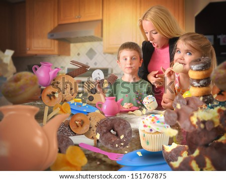 Two children are eating messy junk food snacks such as cookies, donuts and cupcakes in the kitchen with an angry mother. - stock photo