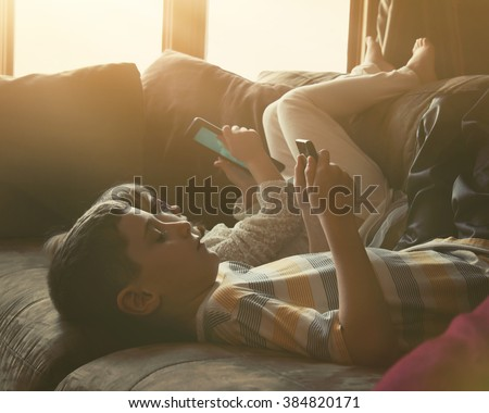 Two Children are laying on a couch at home using internet technology tablets with sunshine coming in the window for a leisure or entertainment concept. - stock photo