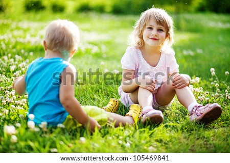 Two children are sitting on green meadow and smile