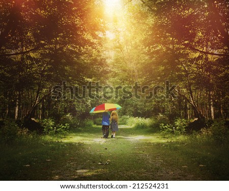 Two children are walking down a sunshine trail in the woods holding a rainbow umbrella for a friendship, hope or happiness concept. - stock photo