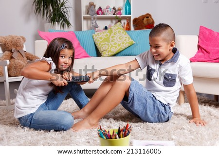 Two children arguing about watching TV - stock photo