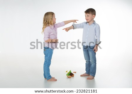 two children blaming each other for a fallen vase of flowers - stock photo