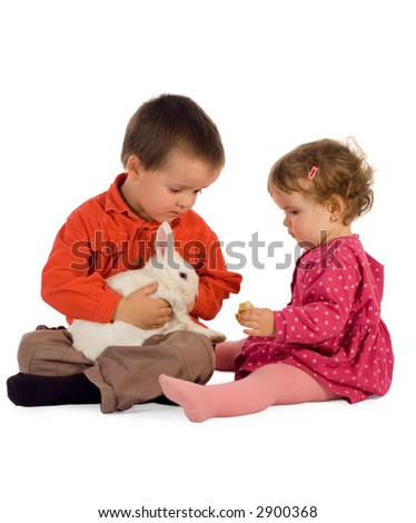 Two children - boy and girl - feeding a cute bunny (easter theme, isolated)