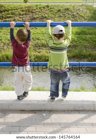 Two children, boys, playing holding a railing by a small river.