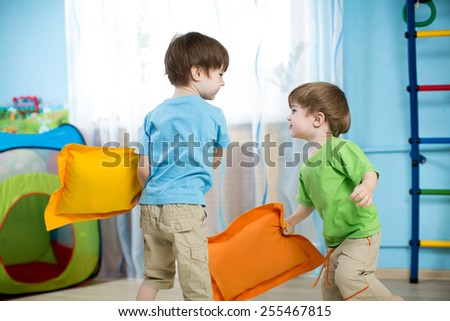 Two children boys playing with pillows at home - stock photo