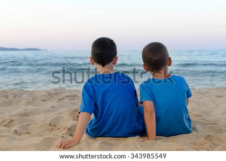 Two children boys sitting together on a sandy beach in the evening - stock photo
