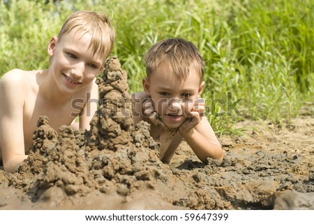 Two children build a sand castle on the river