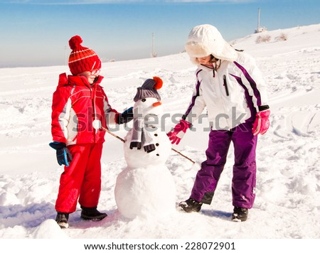Two children building a snowman - stock photo