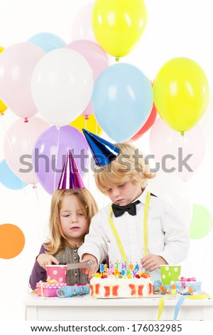 Two children celebrating a birthday with balloons in the background.