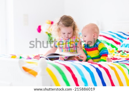 Two children, curly little toddler girl and a funny baby boy, brother and sister, reading a book in a sunny bedroom on a wooden white bed with colorful rainbow bedding enjoying a nice weekend morning - stock photo
