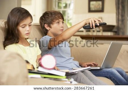 Two Children Distracted By Television Whilst trying To Do With Homework - stock photo