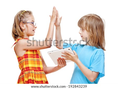 Two Children Doing High Five Gesture after Winning a Game on Tablet  - stock photo