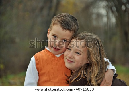 two children embrace on a beautiful fall day - stock photo