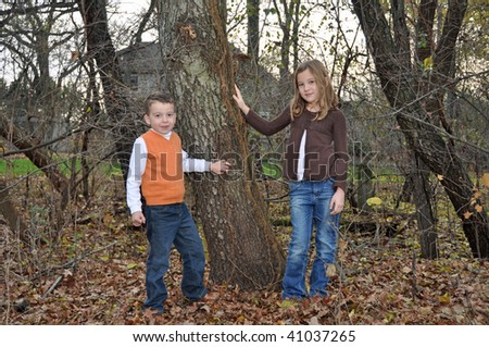 two children enjoy an autumn day in the woods - stock photo