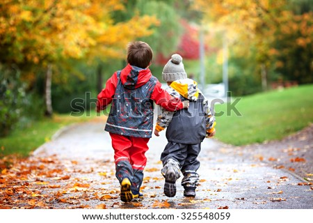 Two children, fighting over toy in the park on a rainy day, autumn time - stock photo