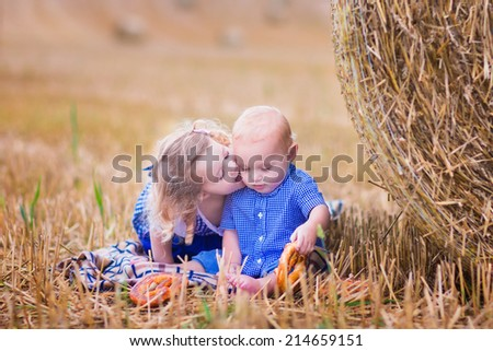 Two children, funny toddler girl and a little baby boy, playing in a field with hay rolls eating pretzels during Oktoberfest in Germany. Sister kissing and hugging her little brother - stock photo