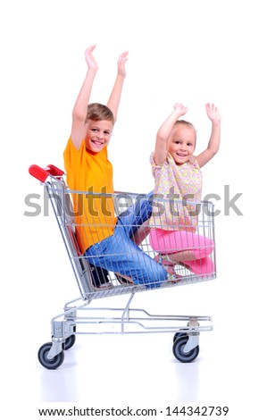 two children - girl and baby - with shopping cart in supermarket - stock photo