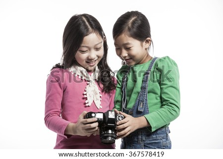 Two children girl(female, woman) hold a camera take a picture each other(together) with smile(happy) for sons(instagram) isolated white at the studio. - stock photo