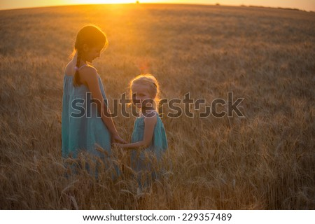 two children girls  at the sunset at the wheat field  - stock photo