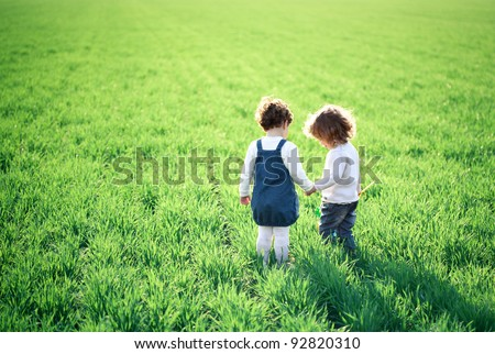 Two children going in spring green field - stock photo