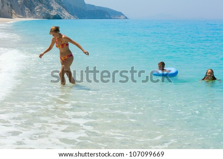 Two children have the water-based recreation on white beach near azure Ionian sea (Egremni, Lefkada, Greece)