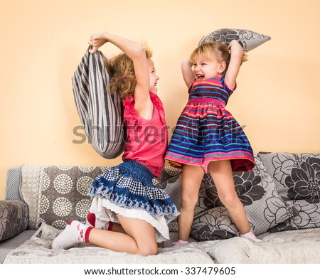 Two children having fun at pillow fight with feathers in the air jumping, laughing and giggling. - stock photo