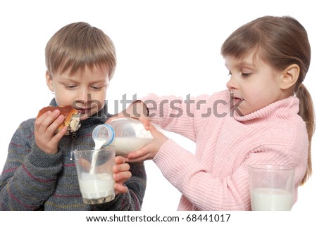 two children having lunch with milk and doughnuts - stock photo