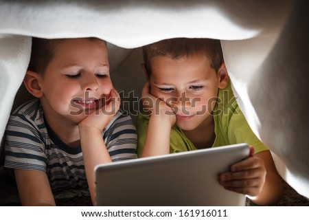Two children holding digital tablet under blanket