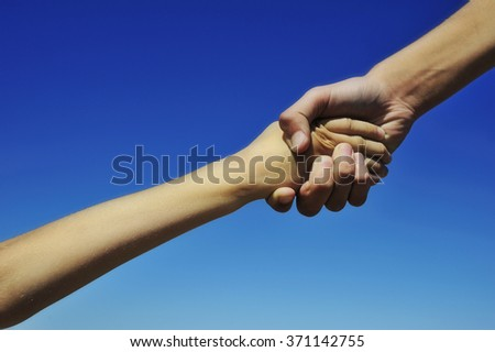 Two children holding hands, close-up - brother helping his younger sister - stock photo