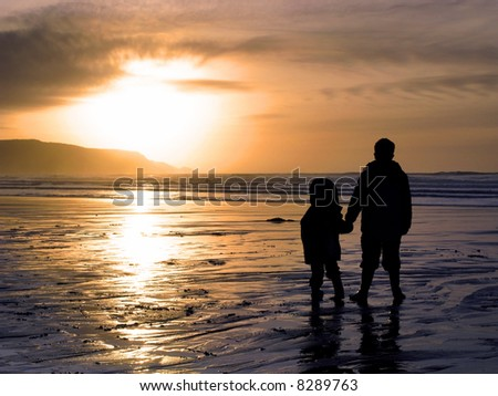 Two children holding hands whilst watching a beach sunset.