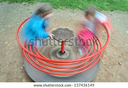 Two children in a red carousel spinning round - stock photo