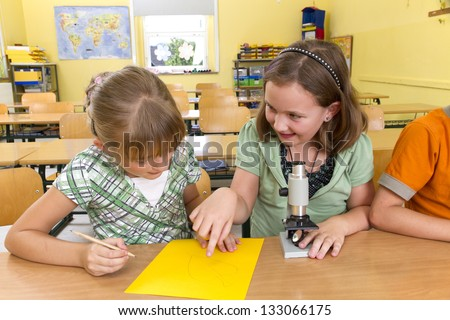 Two children in a yellow classroom. They are leaning with a microscope. - stock photo