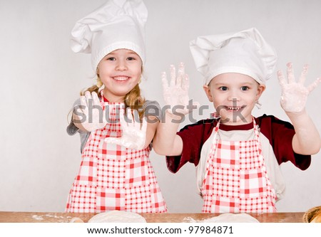 two children in chef's hats showing the palms - stock photo