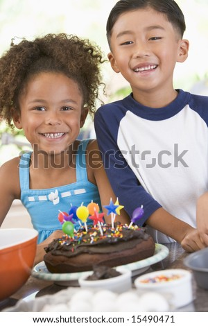 Two children in kitchen with birthday cake smiling - stock photo