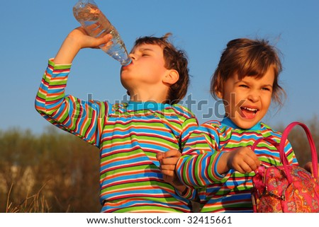 Two children in striped T-shirts,  boy drinks from  bottle,  girl holds bag - stock photo