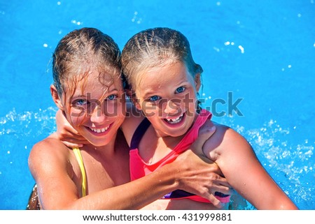 Two children in swimming pool . Children hugging and looking in camera. Summer swimming holiday. Swimming outdoor. Girl holding her sister in her arms. Children activities lifestyle. - stock photo